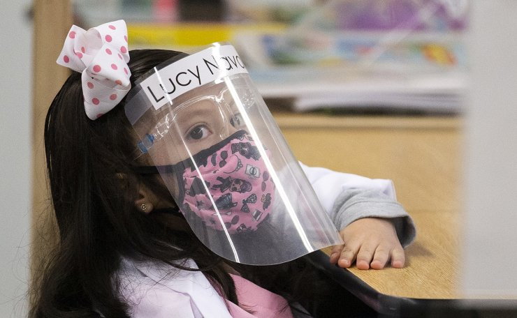 A kindergarten student attends class wearing a face shield and a mask at the Resurrection Catholic School amid coronavirus pandemic as the school reopens its doors for the first time and is celebrating frontline workers in Boyle Heights, East Los Angeles, California, USA, 01 February 2021. EPA