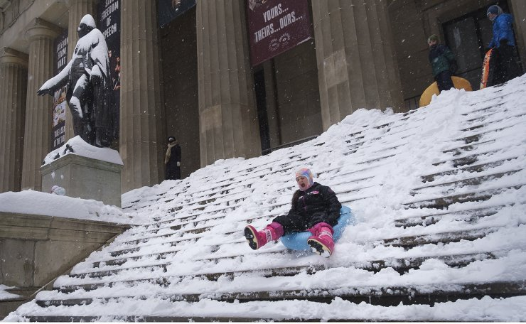 Children sled down the steps of Federal Hall, at left is a snow covered statue of George Washington, as snow falls in New York, New York, USA, 01 February 2021. EPA