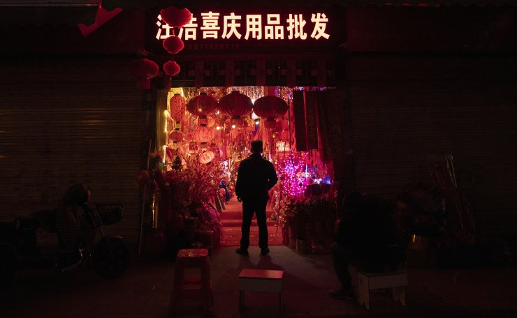 A vendor is silhouetted by decorations in his store ahead of the Year of the Ox Chinese Lunar New Year celebrations in Wuhan in central China's Hubei province on Tuesday, Jan. 26, 2021. A recent resurgence in coronavirus cases in China has prompted authorities to curb Lunar New Year activities, impacting a wide swath of industries from airlines, trains, hotels and restaurants to small shops selling decorations for the Year of the Ox. AP