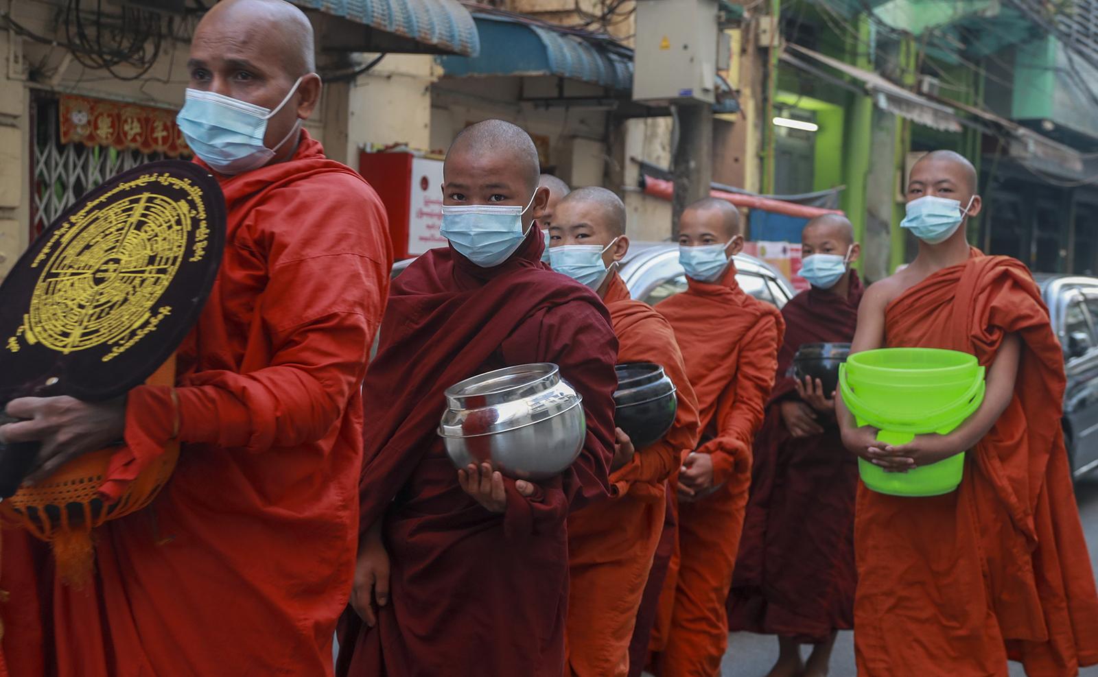Buddhist monks walk begging for alms in Yangon, Myanmar, Tuesday, Feb. 2, 2021. AP
