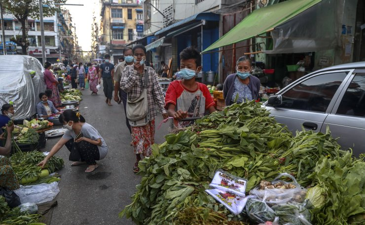 A boy pushes a cart with vegetable in a street market Yangon, Myanmar, Tuesday, Feb. 2, 2021. AP