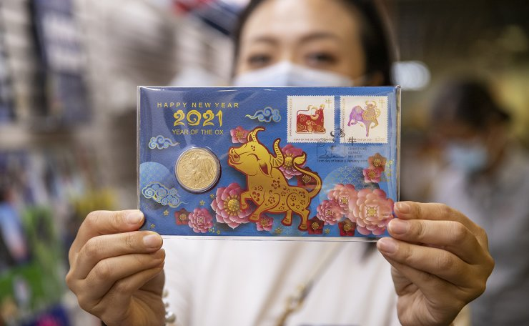 A woman shows a special coin for year of the ox at an Australian Post office, in Sydney, Australia, on Feb. 2, 2021. The Chinese lunar new year falls on Feb. 12, 2021. Xinhua