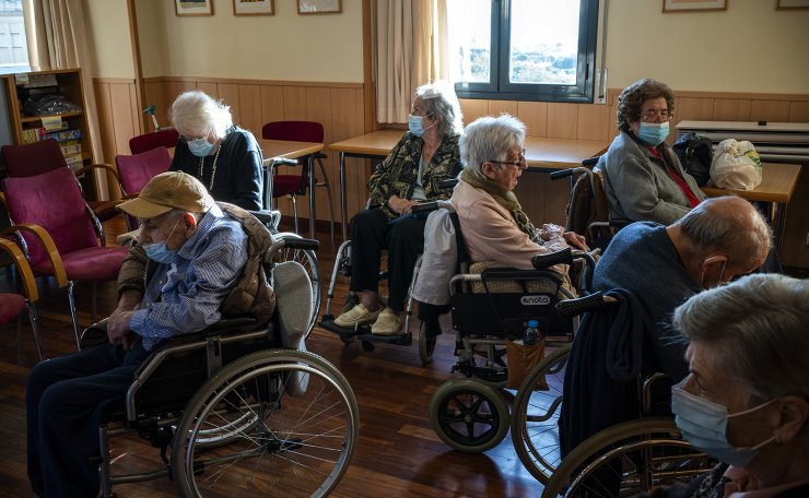People at the the Icaria nursing home in Barcelona, Spain, wait their turn to be vaccinated with the Pfizer-BioNTech COVID-19 vaccine on Tuesday, Feb. 2, 2021. Spain's top coronavirus expert suggests that the coronavirus vaccine manufactured by AstraZeneca should be administered to young people given the lack of evidence on how it performs with older adults. AP