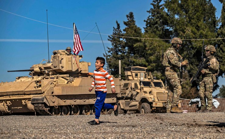 A child runs past US soldiers standing by a Bradley Fighting Vehicle (BFV) during a patrol in the countryside near al-Malikiyah (Derik) in Syria's northeastern Hasakah province on February 2, 2021. AFP