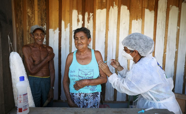 Francisca do Carmo receives the AstraZeneca/Oxford vaccine for the coronavirus disease (COVID-19) by a municipal health worker, as her husband Raimundo do Carmo looks on, along the Solimoes river banks, where Ribeirinhos (river dwellers) live, in Manacapuru, Amazonas state, Brazil, February 1, 2021. Picture taken February 1, 2021. REUTERS