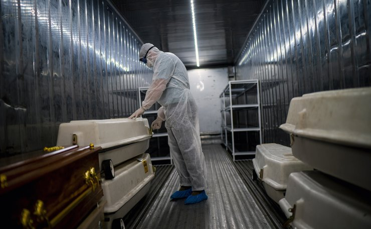 An AVBOB mortuary employee wearing full PPE checks coffins containing the remains of COVID-19 victims in a refrigerated container in Johannesburg, Tuesday, Feb. 2, 2021, one day after South Africa gave a hero's welcome to the delivery of its first COVID-19 vaccines — 1 million doses of the AstraZeneca vaccine produced by the Serum Institute of India. AP