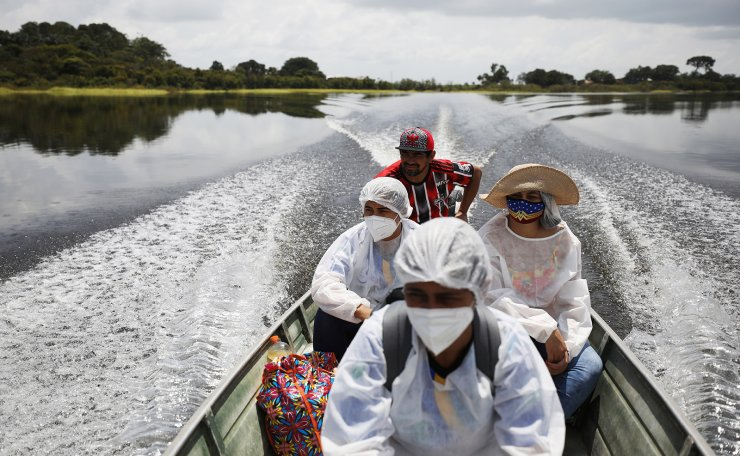 Municipal health workers travel on a boat along the Solimoes river banks, where Ribeirinhos (river dwellers) live, to apply the AstraZeneca/Oxford vaccine for the coronavirus disease (COVID-19) to the residents, in Manacapuru, Amazonas state, Brazil, February 1, 2021. Picture taken February 1, 2021. REUTERS