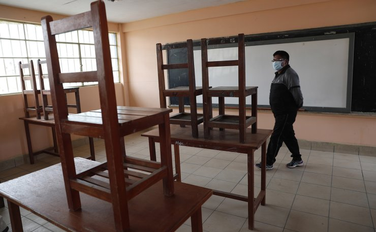 Elsner Laura, wearing a protective face mask amid the COVID-19 pandemic, walks into his classroom at the '1ro de Mayo' school to prove that it remains empty of students, in El Alto, Bolivia, Tuesday, Feb. 2, 2021. Local news reports claimed that children had returned to their classrooms but schools remain closed as students continue with online classes at home due to the pandemic. AP