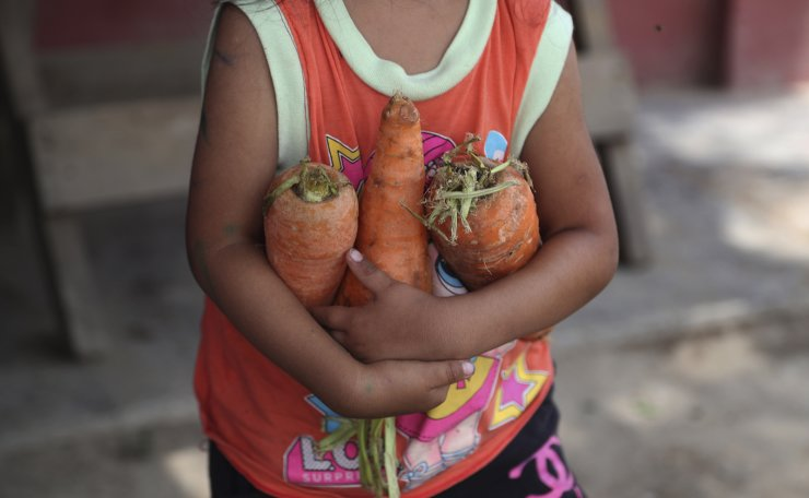A child carries an armful of donated carrots to her mother who is helping prepare lunch at a soup kitchen in the Villa Maria shantytown of Lima, Tuesday, Feb. 2, 2021, amid a second complete lockdown in less than a year as Peru battles a resurgence in COVID-19 cases. The lack of a steady income has forced many families to become dependent of community soup kitchens in some of the capital's poorest neighborhoods. AP