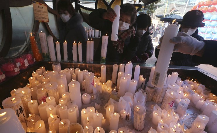 People wearing face masks to help protect against the spread of the coronavirus light candles marking the start of spring according to the lunar calendar at the Jogye Temple in Seoul, South Korea, Wednesday, Feb. 3, 2021. AP