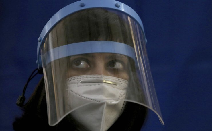 A doctor wears a face mask and shield to protect against the coronavirus while she wait for to receive a Sinopharm coronavirus vaccine at a vaccination center, in Karachi, Pakistan, Wednesday, Feb. 3, 2021. AP