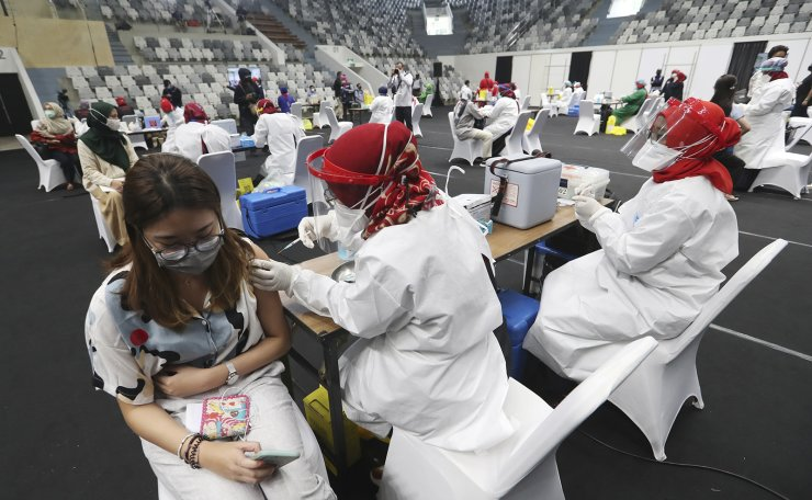 A medical worker receives a shot of COVID-19 vaccine during a mass vaccination for medical workers in Jakarta, Indonesia, Thursday, Feb. 4, 2021. AP
