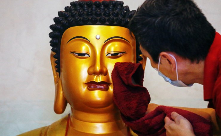 A man wearing a protective face mask wipes a Buddha statue ahead of the Chinese Lunar New Year celebration following the coronavirus disease (COVID-19) outbreak, at a temple in Jakarta, Indonesia, February 4, 2021. REUTERS