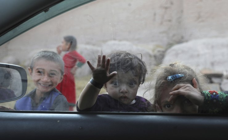 Afghan children look into a window of a car on the outskirts of Jalalabad city east of Kabul, Afghanistan, Thursday, Feb. 4, 2021. AP