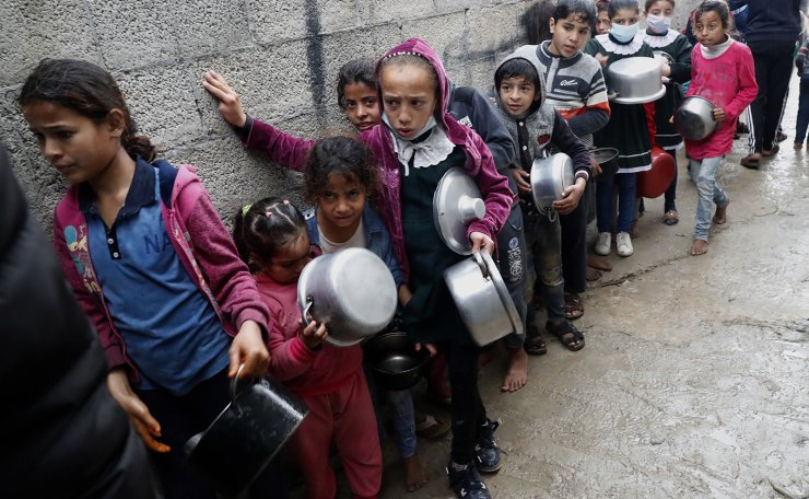 Palestinian children wait in queue while hold pots to receive free meals of green pea stew cooked by Samera Abu Amra, unseen, to distributes for poor residents in Gaza City, Feb. 4, 2021. Amra cooks the meals with money sent by benefactors to help feed the poor as poverty and unemployment rates hover around 50%. AP