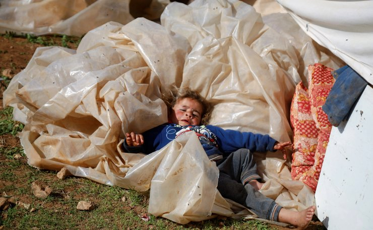 A Palestinian child lies on a plastic sheet in the village of Khirbet Humsah, which was razed by Israeli forces, in Jordan Valley in the Israeli-occupied West Bank February 4, 2021. REUTERS