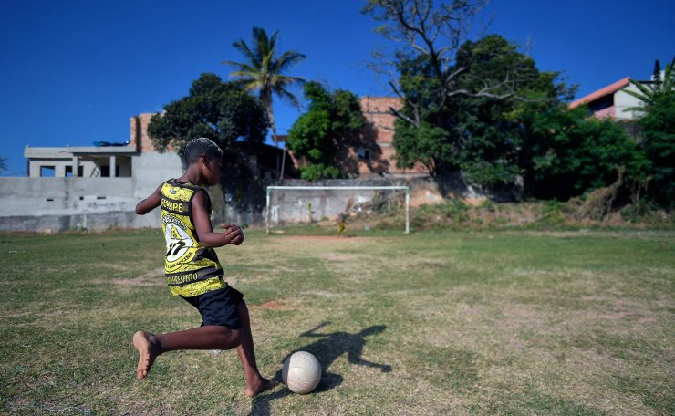 A youngster plays at a field where Brazilian Palmeiras footballer Breno Lopes used to play as a child, in Belo Horizonte, Minas Gerais state, Brazil, on February 3, 2021. AFP