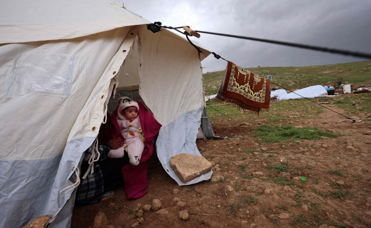 A young child is held by his mother inside a tent as Israeli forces demolish the Bedouin village of Khirbet Humsah near Tubas city in the Jordan Valley on February 4, 2021. AFP