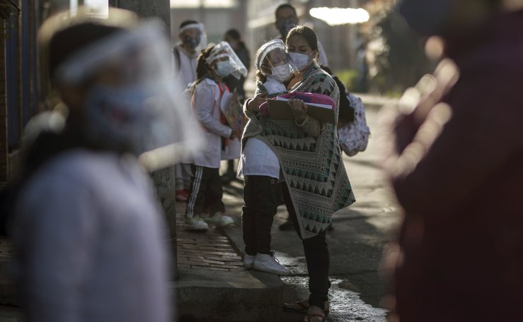 Parents and children wearing COVID-19 protection gear socially distance to enter Liceo Lunita, a private school, on the first day back to in-person class since Spring last year, in Chia on the outskirts of Bogota, Colombia, Friday, Feb. 5, 2021. AP