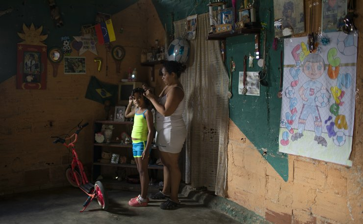 Yangervis Blanco, 7, stands still as her mother helps her prepare for a homespun beauty pageant in the Antimano neighborhood of Caracas, Venezuela, Friday, Feb. 5, 2021. Neighbors in the hillside barrio gathered for the carnival pageant tradition to select their child queen for the upcoming festivities. AP