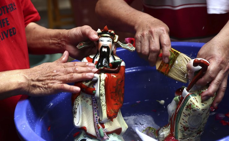Chinese god statues is cleaned in preparation for the upcoming Lunar New Year celebration at a temple in Tangerang, Indonesia, Saturday, Feb. 6, 2021. AP