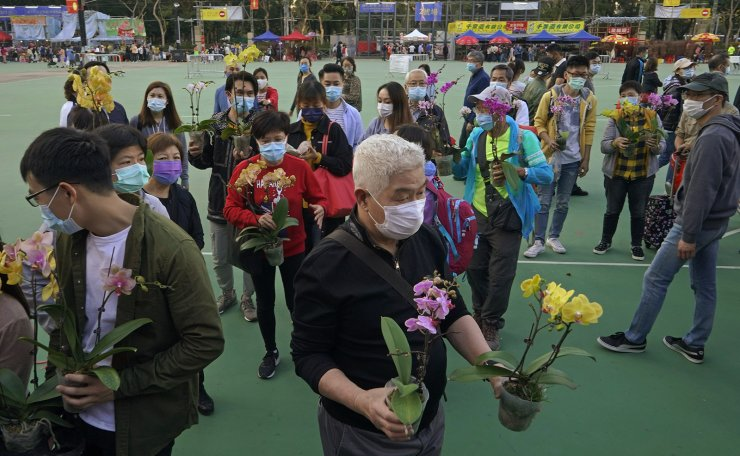 Customers wearing face masks to protect against the spread of the coronavirus, purchase orchids at the flower markets in Victoria Park of Hong Kong, Saturday, Feb. 6, 2021. Traditional Lunar New Year flower markets opened Saturday in Hong Kong, after a government virus policy U-turn. At the biggest venue, Victoria Park next to the popular downtown shopping district of Causeway Bay, the eerie emptiness is in stark contrast to the usual bustle of capacity crowds. AP