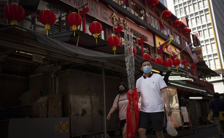 A Chinese couple wear face mask walks with Chinese lunar new year decoration at China town in Kuala Lumpur, Malaysia, Sunday, Feb. 7, 2021. The movement control order (MCO) currently enforced across the country, has been extended to Feb. 18, effectively covering the Chinese New Year festival that falls on Feb. 12 this year. AP