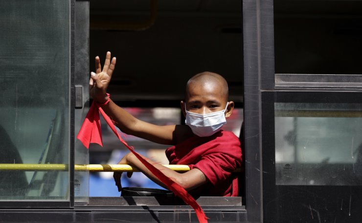 A young Buddhist novice, wearing a red strip of cloth around his wrist, flashes the three-finger salute, a symbol of resistance against the military coup, from inside a vehicle in Yangon, Myanmar, 07 February 2021. EPA