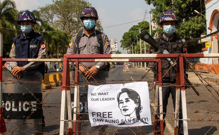 Police stand guard as a poster demanding the release of elected leader Aung San Suu Kyi is seen on a police barricade, in Yangon, Myanmar, February 7, 2021. REUTERS