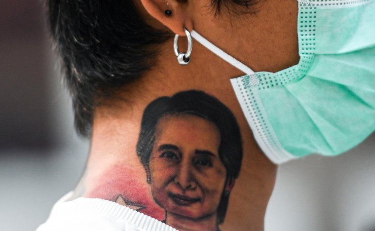 A Myanmar citizen with a tattoo of leader Aung San Suu Kyi looks on during a protest against the military coup in Myanmar outside United Nations venue in Bangkok, Thailand February 7, 2021. REUTERS