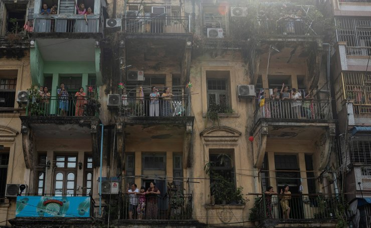 People watch from their balconies a protest against the military coup and demanding the release of elected leader Aung San Suu Kyi, in Yangon, Myanmar, February 7, 2021. REUTERS