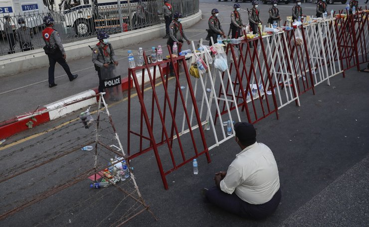 A demonstrator (front) sits in front of a barricade as policemen stand guard near the Yangon City Hall during a protest against the military coup in Yangon, Myanmar, 07 February 2021. EPA