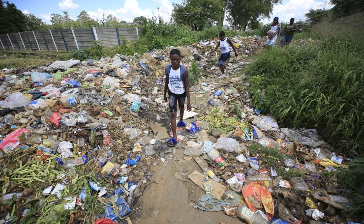Children walk past uncollected garbage in the township of Glen View, Harare, Zimbabwe, 07 February 2021. Residents of Glen View township experience several sewer bursts since October 2020 as the local authorities  workers are on strike. There are fears of new cholera outbreaks again in this township, which always has been the epicentre of the disease in Zimbabwe.  EPA