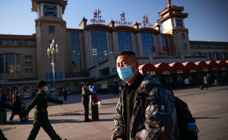 Travelers wearing face masks arrive at Beijing Railway Station ahead of Lunar New Year celebrations as the government urges people to avoid travel because of outbreaks of the coronavirus disease (COVID-19), in Beijing, China February 8, 2021. REUTERS