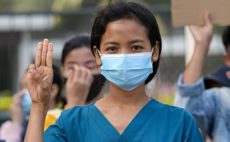 A nurse show the three-finger salute as she takes part in a protest against the military coup and to demand the release of elected leader Aung San Suu Kyi, in Yangon, Myanmar, February 8, 2021. REUTERS