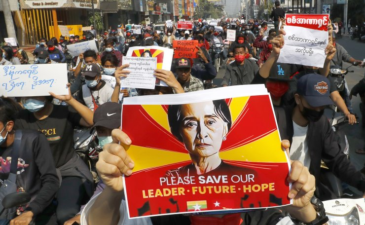 A protester holds an image of deposed Myanmar leader Aung San Suu Kyi as fellow protesters march around Mandalay, Myanmar on Monday, Feb. 8, 2021. AP