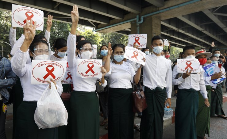 Teachers flash the three-fingers salute, a symbol of resistance, during a protest against the military coup, at Hledan junction in Yangon, Myanmar, 08 February 2021. EPA