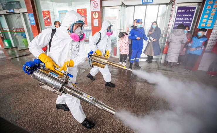 This photo taken on February 7, 2021 shows workers disinfecting a long distance bus station in Bijie, in China's southwest Guizhou province, as authorities prepare for a travel peak ahead of the Lunar New Year, which ushers in the Year of the Ox on February 12. AFP