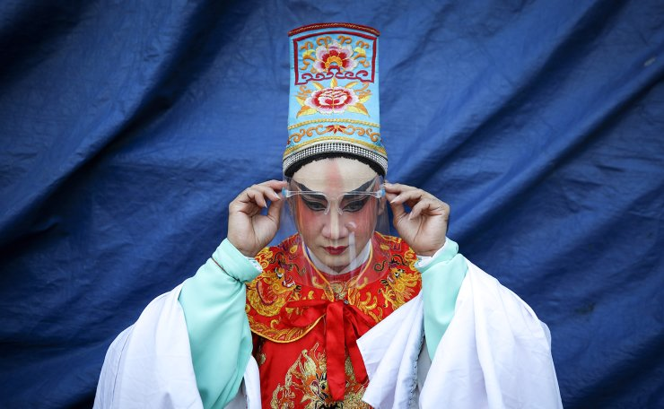 An actor adjusts his protective face shield as he prepares to go on stage during a Chinese Opera performance ahead of the upcoming Lunar New Year in Bangkok, Thailand, 04 February 2021 (issued 08 February 2021). The Sai Yong Hong opera troupe is one of the few remaining troupes in Thailand. The traditional Chinese Opera has been a part of Thai culture for centuries, with performances taking place on various occasions in the Thai-Chinese community. The Chinese Opera is a spectacle combining song, dance, acting, poetry and martial arts. Usually hired by local Chinese shrines to perform in Bangkok's Chinatown during the festivals, the performers, most of them descendants of ethnic Teochew Chinese, wear colorful costumes and elaborate make-up to bring mythical stories to life. EPA