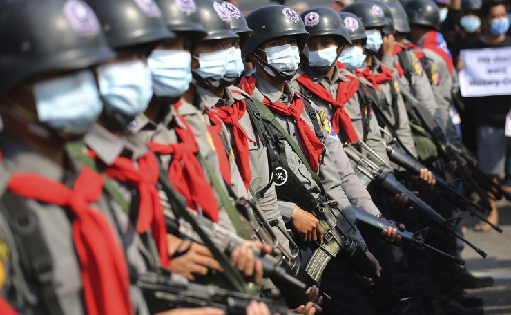 Armed riot police are seen near protesters in Naypyitaw, Myanmar on Monday, Feb. 8, 2021. AP