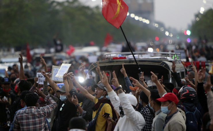 Protesters hold a picture of deposed leader Aung San Suu Kyi  in Yangon, Myanmar on Monday, February 8, 2021. AP