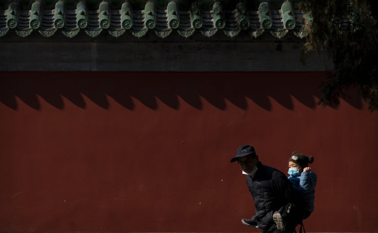 A man carries a boy wearing a face mask to protect against the spread of the coronavirus at Ditan Park in Beijing, Tuesday, Feb. 9, 2021. The park, which would normally host one of the biggest temple fairs in China's capital during the upcoming Lunar New Year holiday, is largely quiet this year as authorities canceled most public events in an effort to maintain control of the COVID-19 pandemic. AP