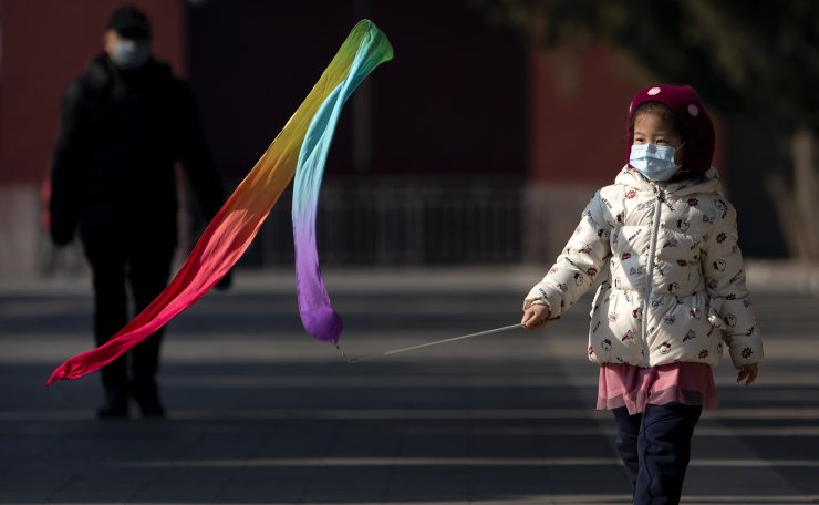 A girl wearing a face mask to protect against the spread of the coronavirus plays with a toy at Ditan Park in Beijing, Tuesday, Feb. 9, 2021. AP