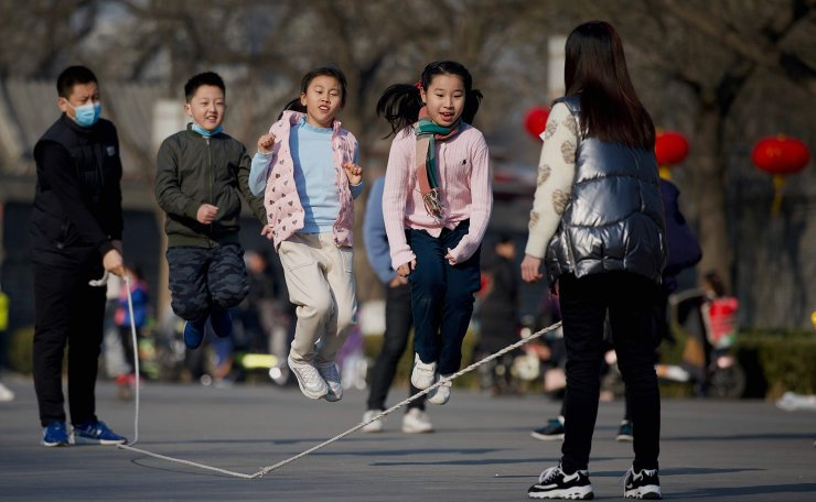 Children play a jump rope game in a park in Beijing on February 9, 2021. AFP
