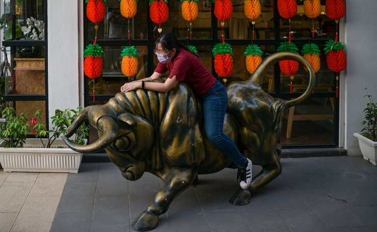 A woman sits on a bull statue as she poses for photos to mark the Lunar New Year, which marks the Year of the Ox, outside a shop in Cyberjaya on February 9, 2021. AFP