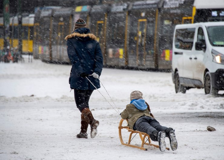 A woman pulls a child on a sledge at Berlin's Alexanderplatz square on February 9, 2021, as temperatures in the German capital remain at around minus ten degrees Celsius. AFP