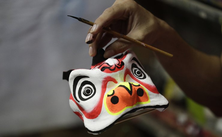 A miniature lion head is carried as it is prepared to be painted as a dragon and lion dance group seek other ways to earn a living at a creekside slum at Manila's Chinatown, Binondo Philippines on Feb. 3, 2021. The Dragon and Lion dancers won't be performing this year after the Manila city government banned the dragon dance, street parties, stage shows or any other similar activities during celebrations for Chinese New Year due to COVID-19 restrictions leaving several businesses without income as the country grapples to start vaccination this month. AP