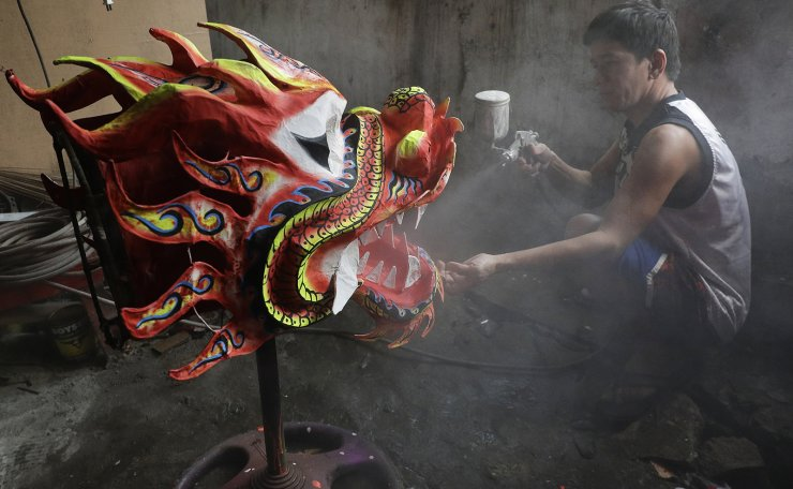 Robert Sicat sprays a protective coating on a Dragon head at a creekside slum at Manila's Chinatown, Binondo Philippines on Feb. 4, 2021. AP