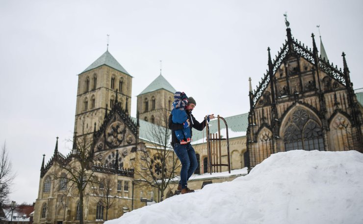 Jamie from Scotland and his son walk up a hill with a sledge in front of the cathedral of Muenster, western Germany, on February 10, 2021. AFP
