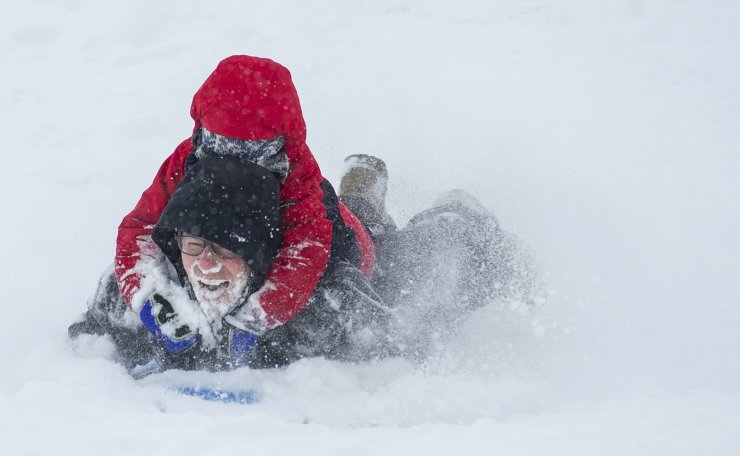 Samuel Braun, 6, let his dad, Dave, take the brunt of the frozen powder while sledding in the snowfall Friday Feb. 12, 2021 in Walla Walla, Wash. Both came up smiling. AP